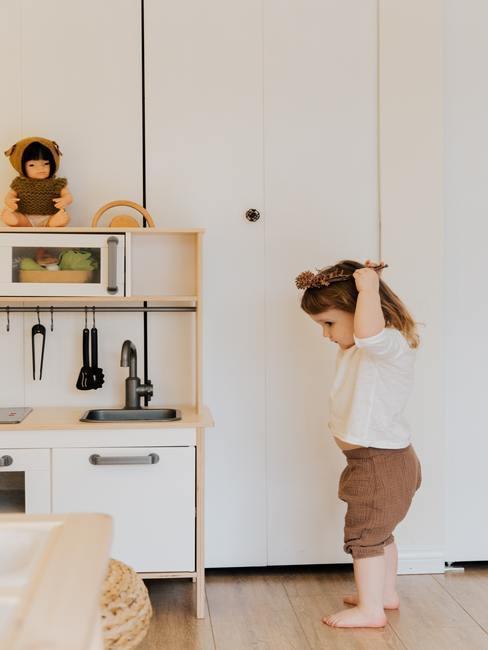 Peuter met houten speelkeuken in de kleuren wit, bruin, beige en okergeel