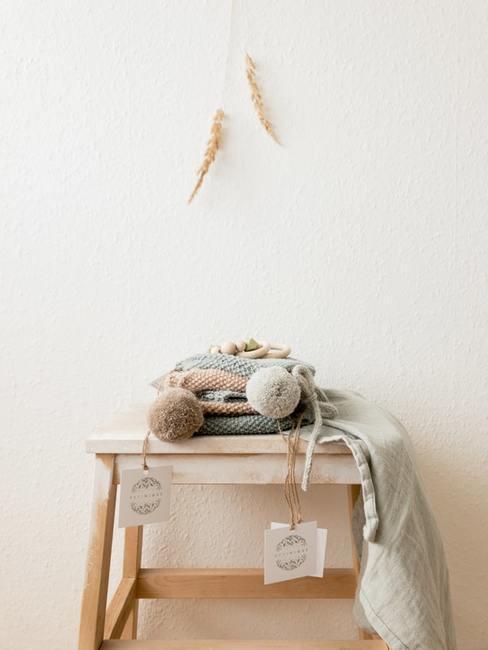 babykleding op houten krukje