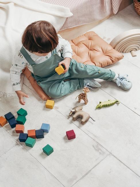 kind in groen pkje speelt op grijze vloer met houten blokken