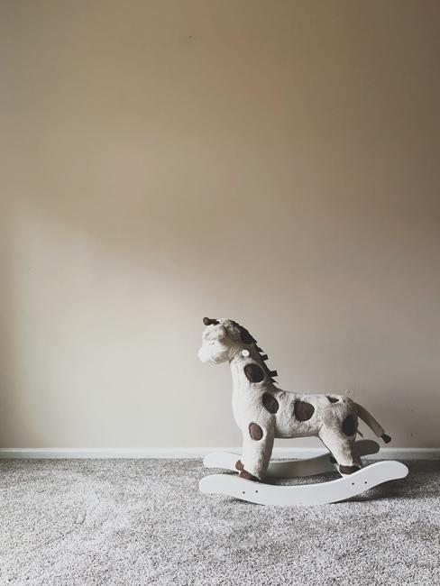 schommeldier in wit en bruin op grijs vloerkleed met grijze achtergrond