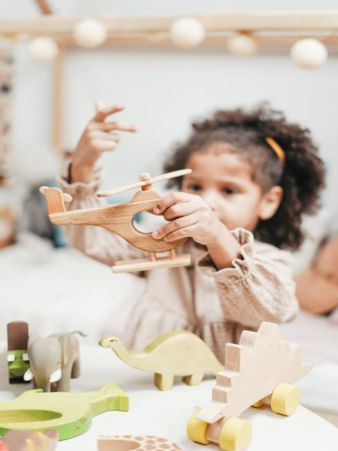 kind speelt met houten speelgoed
