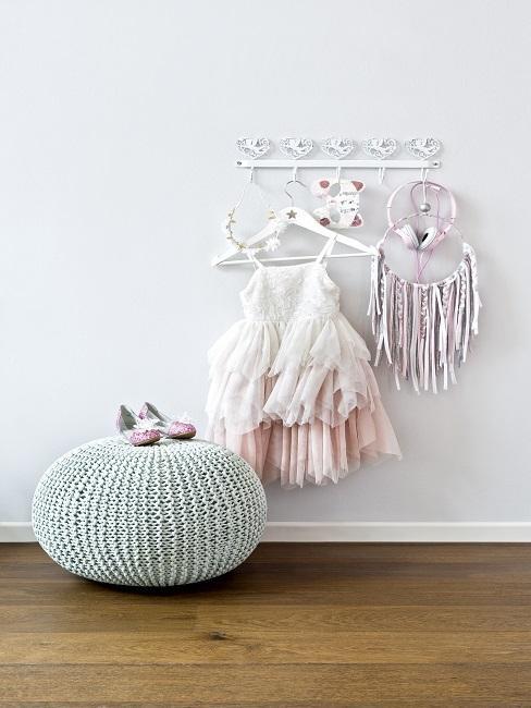 Babykamer grijd - meisjesklren hangen op wandhaak aan witte muur met grijs-groene poef ervoor op houten vloer