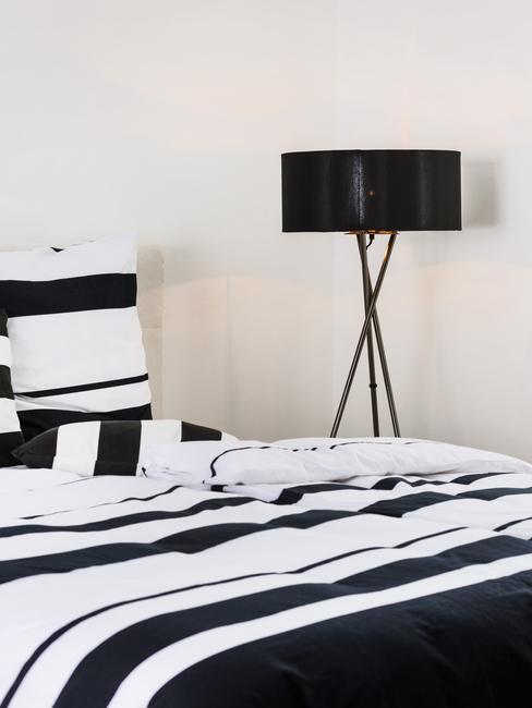 Zwart-witte lakens op het bed in de slaapkamer naast een zwarte vloerlamp