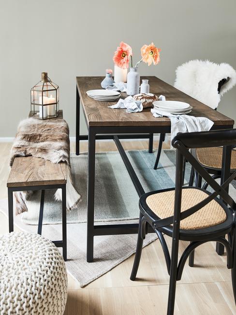 Houten eettafel met stoelen en zitbank met plaid