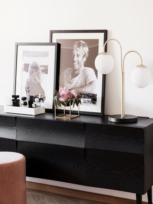 Zwarte sideboard met ingeliste print en goudkleurige tafellamp
