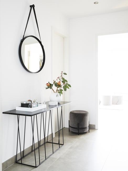 Zwarte houten sidetable met wit dienblad en witte vaas met bloemen en spiegel aan de muur