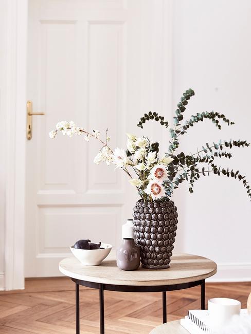 Grote vaas van aardewerk met bloemen op houten bijzettafel