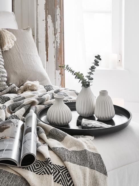 Witte vazen op zwart dienblad op een bed