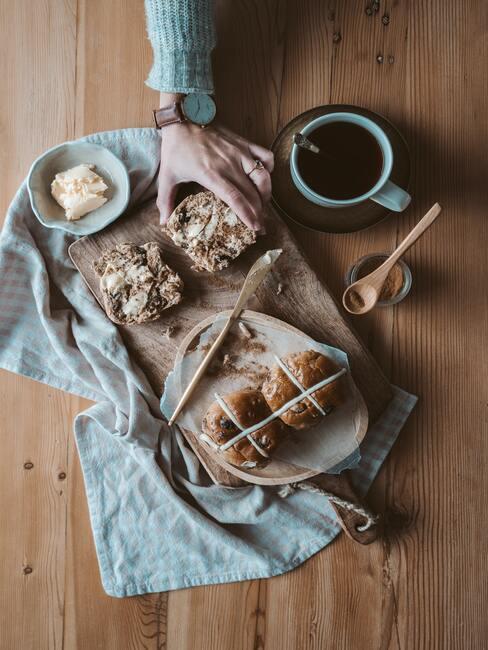 Vers gebakken brood met boter en thee met honing op een houten snijplank