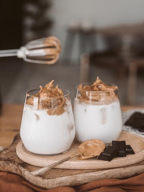 Kersthapjes: zoet dessert gemaakt van slagroom en cacaorooms in een glas op een houten bord
