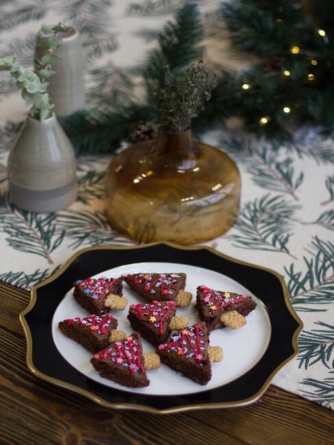 Koekjes op een bord met kerstversiering op een houten tafel met een tafelkleed in een kerst patroon