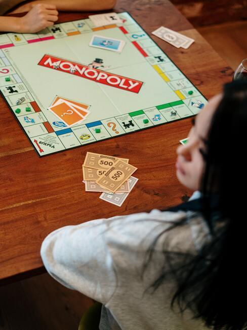 Sinterklaas spelletjes: vrouw die monopolie speelt met vrienden