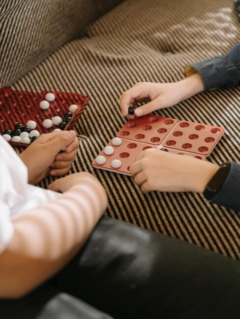 Kinderen spelen een spel op een zachte bank