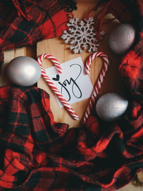 Kerstversiering in rood en zwart op een houten tafel