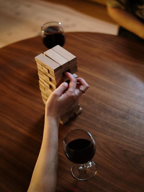 Vrouw die jenga speelt op houten salontafel