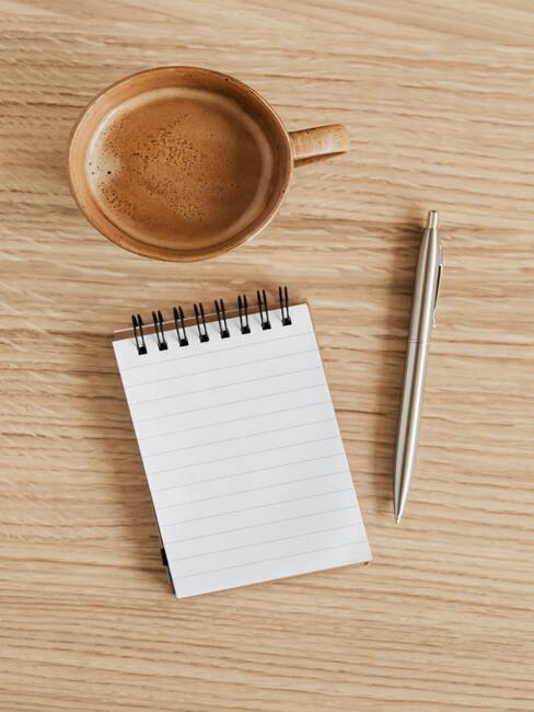 Notebook, pen en koffiemok op een houten tafel