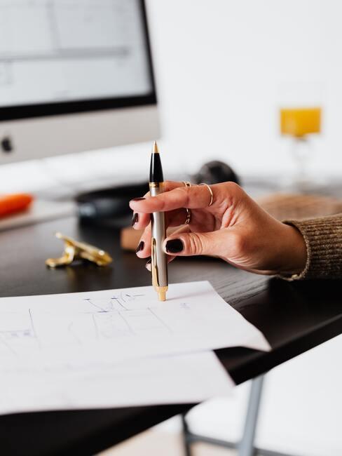 Een vrouw met een vulpen in haar hand die een notitie op een wit blad maakt