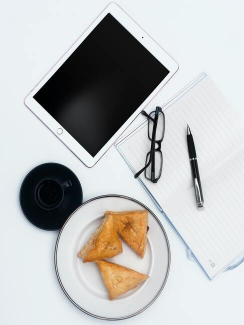 Notebook, brillen, pen en plaat met croissants op een witte tafel