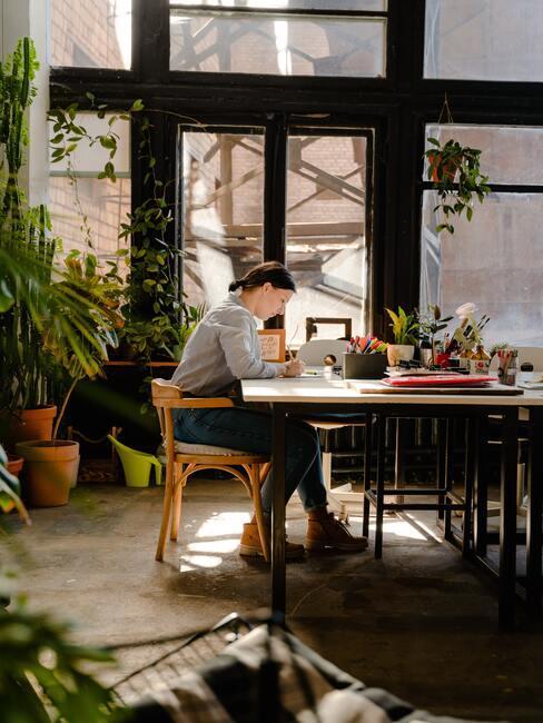 Vrouw zit aan een houten tafel met metalen poten in de keuken