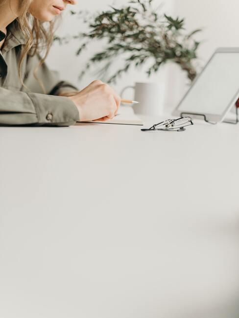 Verlanglijstje maken: vrouw zit aan een witte tafel met een kopje koffie