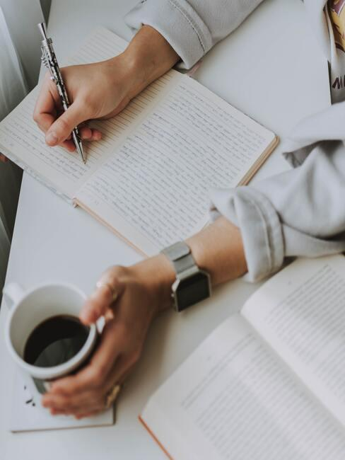 Verlanglijstje maken: vrouw zit aan een witte tafel met een kopje koffie en maakt notities