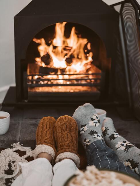 Een paar dat bij de open haard ligt in sokken met een kerstpatroon