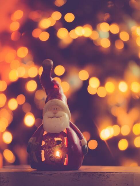 Schoen zetten: decoratieve porseleinen kerstman op een houten tafel naast de kerstboom