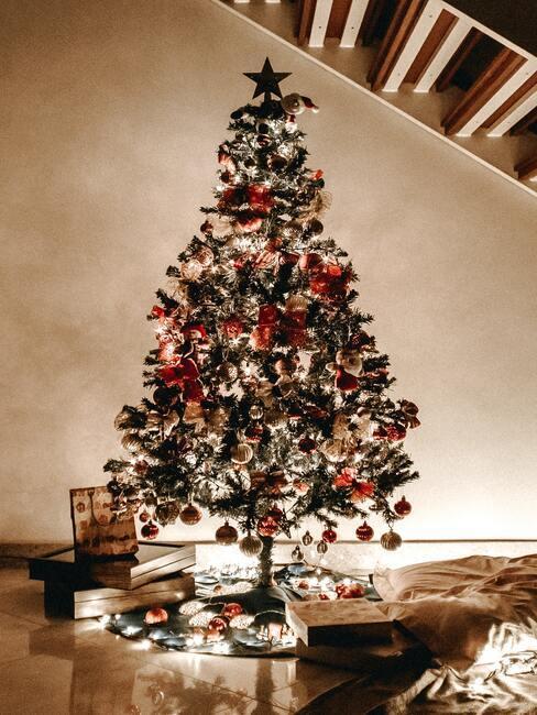 Schoen zetten: versierde kerstboom met lichtjes en kerstballen en cadeautjes eronder