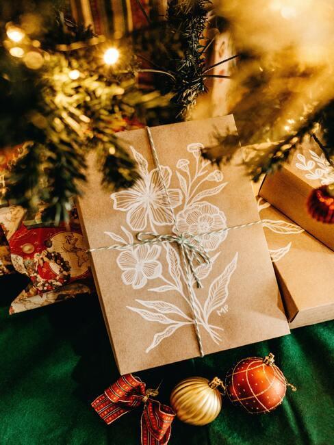 Klassiek verpakt cadeau in papier en lint dat onder de kerstboom ligt
