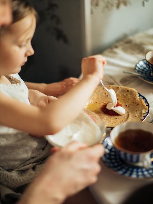Een meisje maakt pannenkoeken klaar voor het avondeten