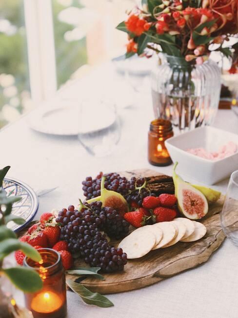 Een bord met kaas, vleeswaren en fruit op een wit tafelkleed naast een transparante vaas met bloemen