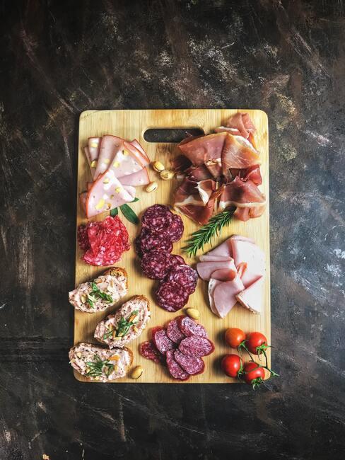 Een bord met kazen en vleeswaren op een marmeren aanrecht