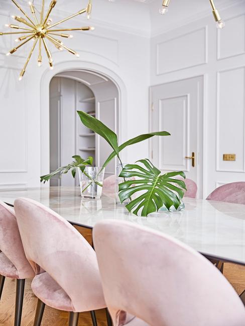 Fluwelen stoelen in lichtroze naast een witte eettafel met transparante vaas met bloemen en goudkleurige hanglamp