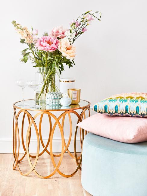 Goudkleurige bijzettafel met transparante vaas met bloemen en geurkaars