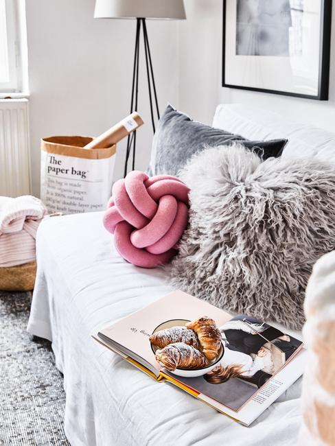 Een witte zitbank met sierkussens in grijs en roze naast een wasmandje