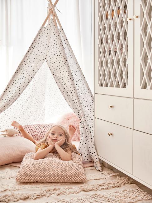 Het meisje ligt in een tipi-tent op zachte roze kussens