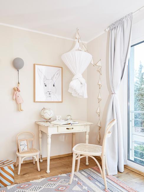 Kinderkamer inspiratie: een kamer in beige en wit met ook een wit bureau en stoel, met ingelistje print en decoratieve objecten op de muur