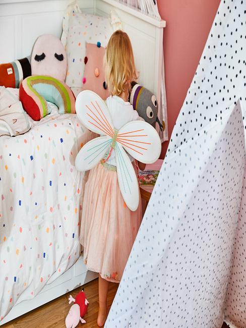 Wit beddengoed met een stippenpatroon naast de tipi
