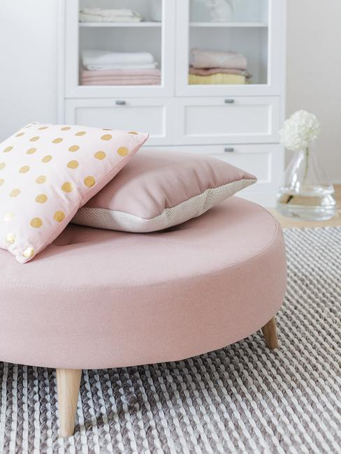 Roze fluwelen poef met sierkussens in roze op grijs zacht vloerkleed