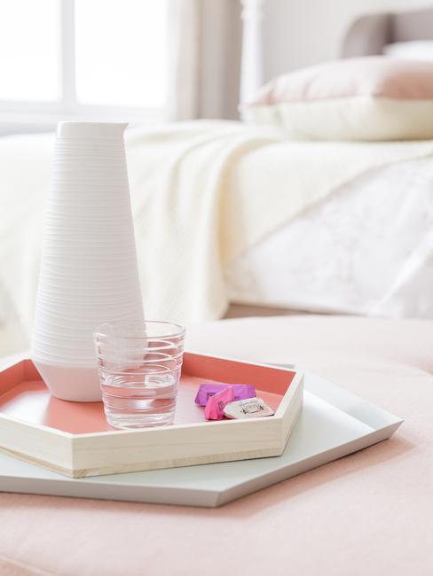 Wit dienblad met witte vaas op roze bijzettafel