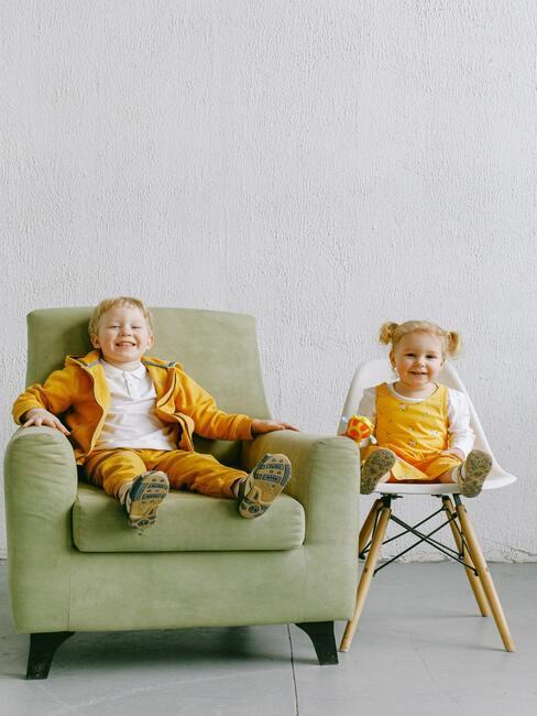 In het geel geklede broer en zus zitten op een groene fauteuil en een witte stoel