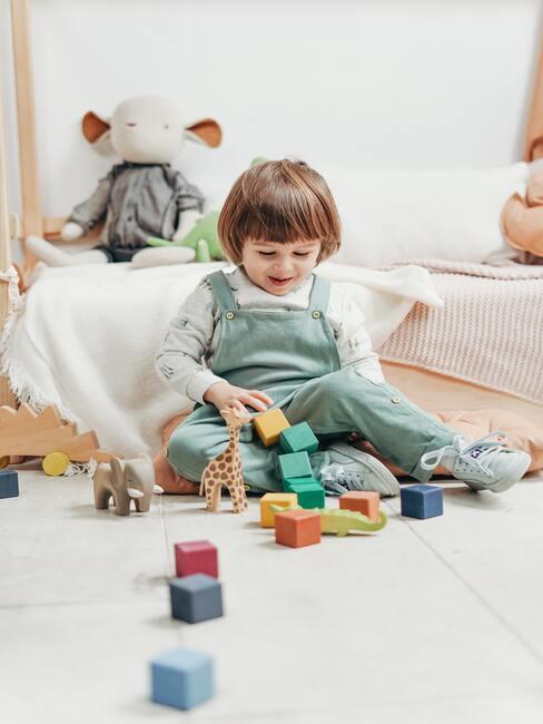 Een jongen speelt met Lego in een witte kamer