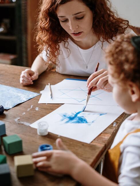 Klein meisje tekent met moeder op een houten tafel