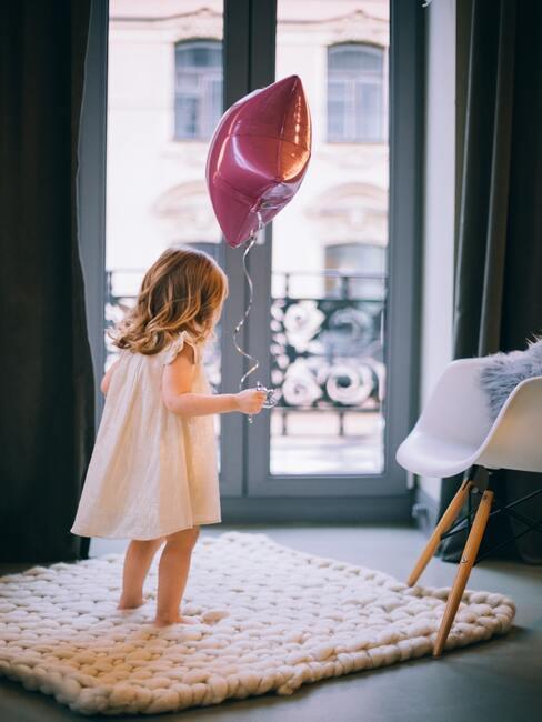 Kidsroom: het meisje houdt een roze ballon in haar hand