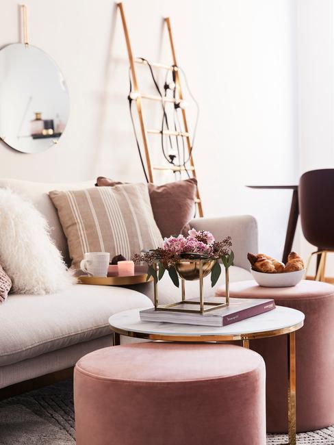 Decoratie ladder met lichtjes naast een comfortabele zitbank in creme kleur met roze kussens en roze poef