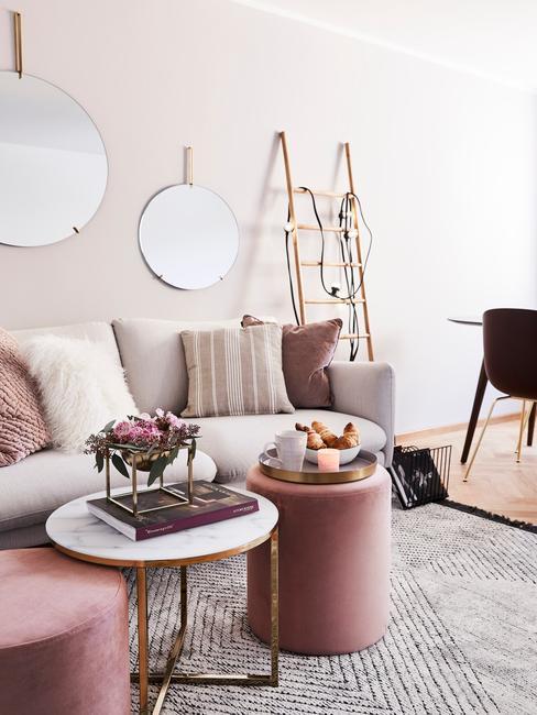 Grijze fluwelen zitbank met kussens in roze naast een roze poef