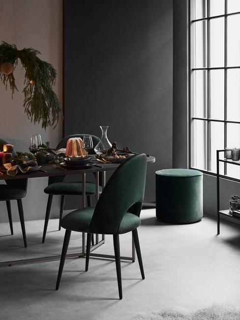 Woonkamer in grijs met groene fluwelen stoelen naast een houten stoel