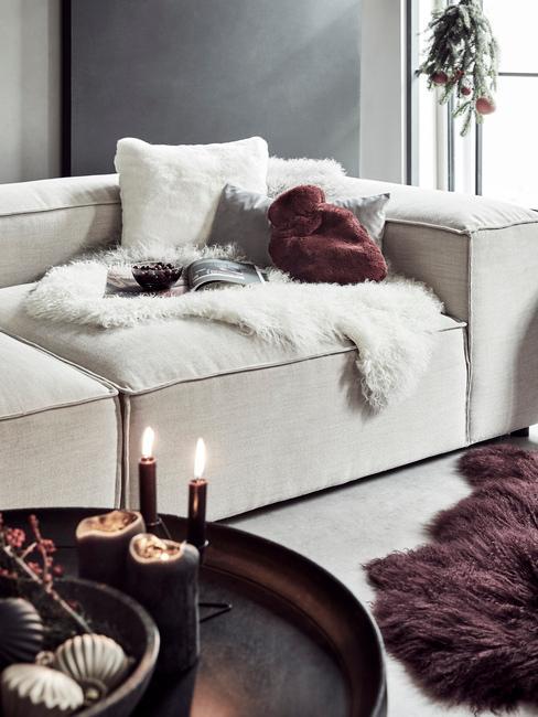 Witte zitbank met schapenvacht naast een zwarte salontafel