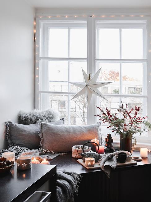 Vensterbank in grijs met sierkussens, lichtslinger, witte lichtster en bloemen in vaas