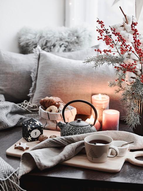 Raamdecoratie voor kerst: sierkussens in grijs, kaarsen, vaas met bloemen